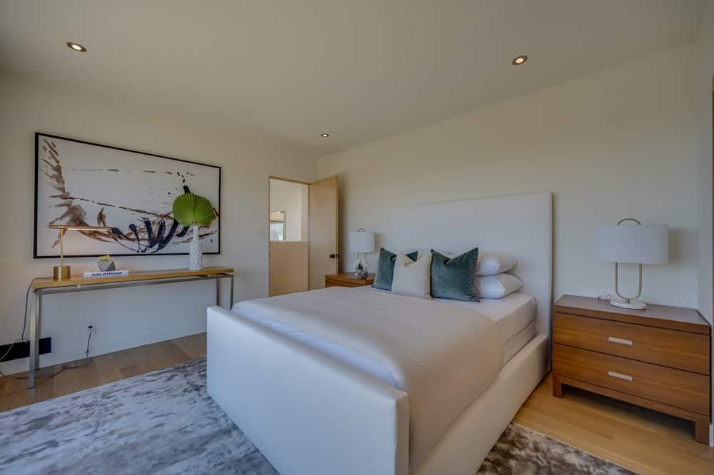 The cushioned bed of this bedroom is flanked by two wooden bedside drawers that match the hardwood flooring. Image courtesy of Toptenrealestatedeals.com.