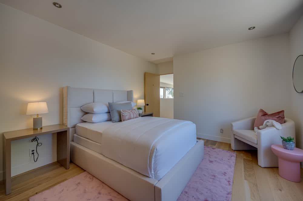 This is a kid's bedroom with a pink area rug under the bed and reading nook on the far corner. Image courtesy of Toptenrealestatedeals.com.