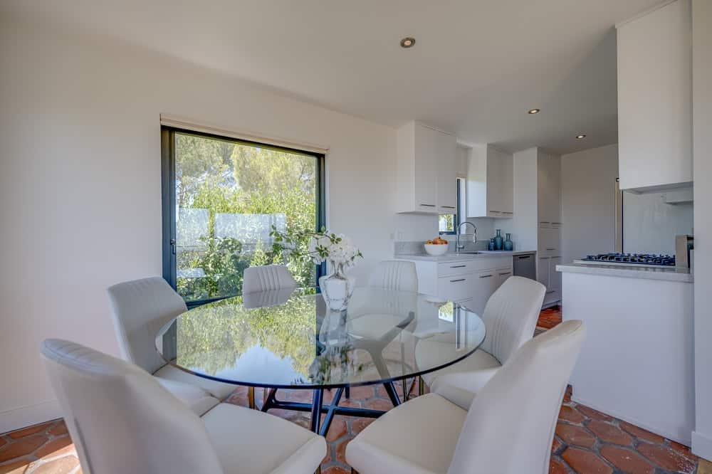 This is a close look at the dining area with a large round glass-top dining table surrounded by beige cushioned chairs. Image courtesy of Toptenrealestatedeals.com.
