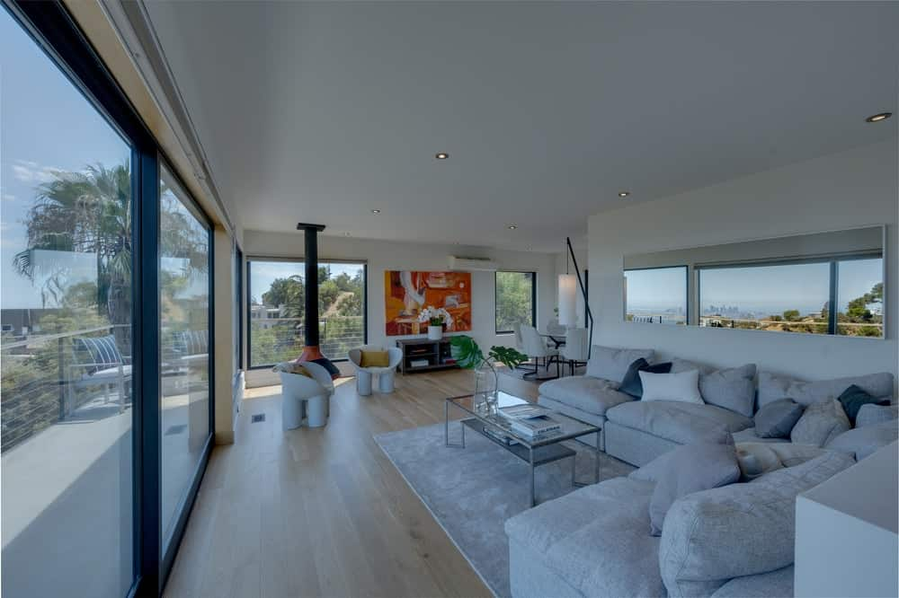 This is the family room area of the great room with a large L-shaped sectional sofa paired with a glass-top coffee table. Image courtesy of Toptenrealestatedeals.com.