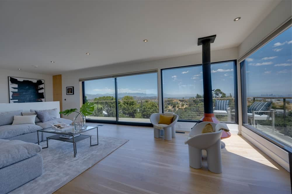 The family room is brightened by the glass walls that can slide and lead to the balcony. Image courtesy of Toptenrealestatedeals.com.