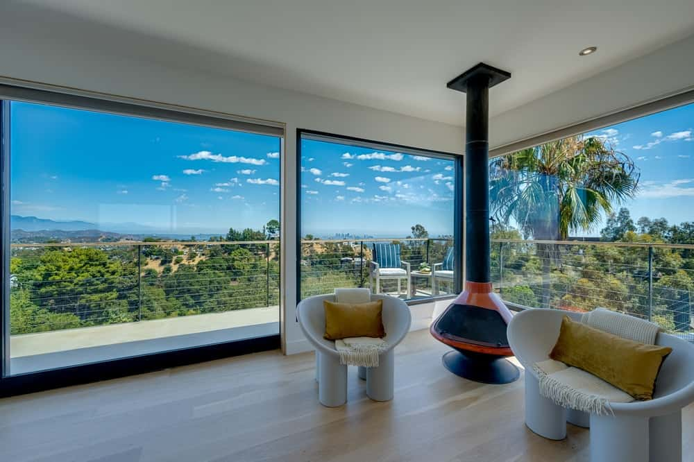This is a closer look at the fireplace that is at the far corner of the family room area flanked by two comfortable chairs illuminated by glass walls. Image courtesy of Toptenrealestatedeals.com.