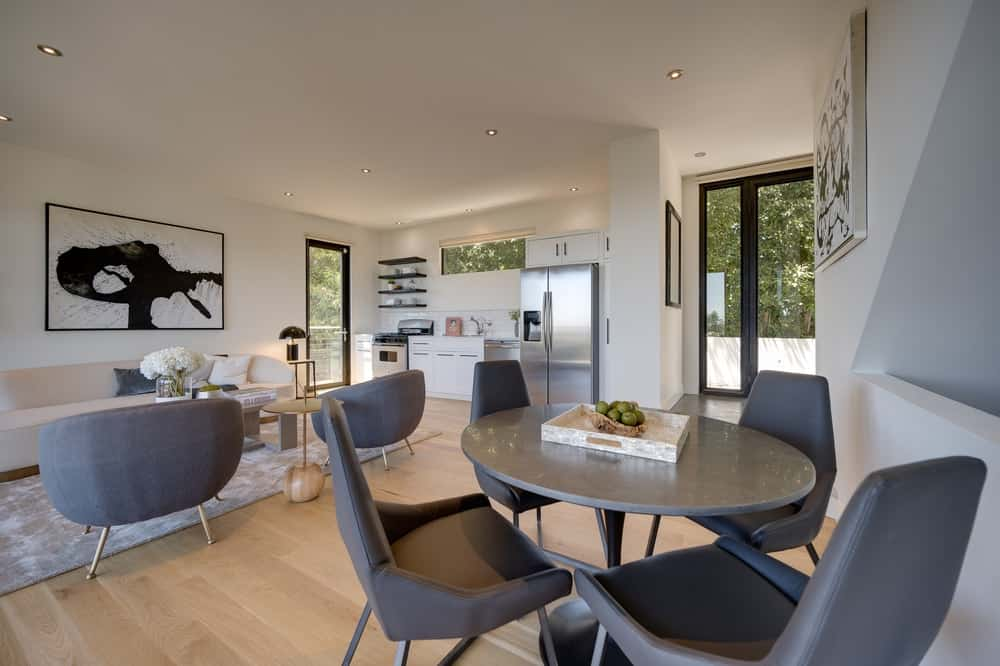 This is one of the great rooms of the house with an open design. It has a living room, dining area and a small kitchen on the far side. Image courtesy of Toptenrealestatedeals.com.
