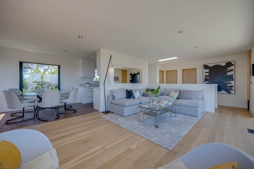 This great room also contains the family area with a large L-shaped sectional sofa that pairs well with the gray area rug. Image courtesy of Toptenrealestatedeals.com.
