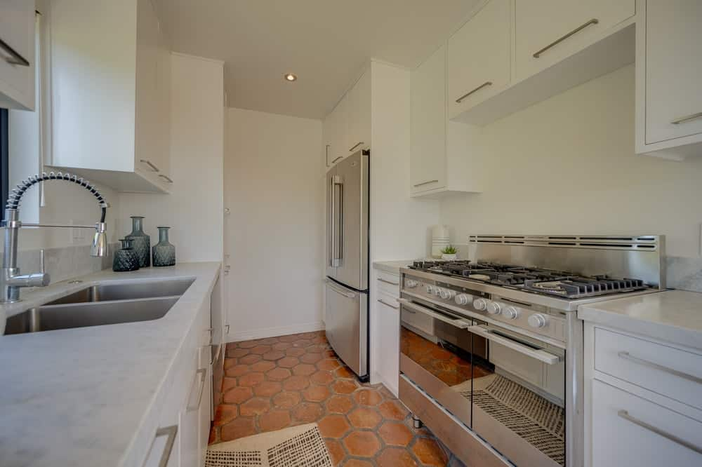 This is the kitchen with large stainless steel appliances that stand out against the light beige walls and terracotta flooring tiles. Image courtesy of Toptenrealestatedeals.com.