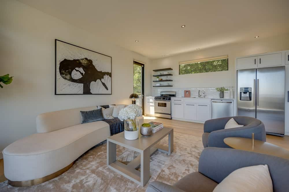This is the living room with a large beige sofa that matches the walls, ceiling and coffee table over the area rug. Image courtesy of Toptenrealestatedeals.com.