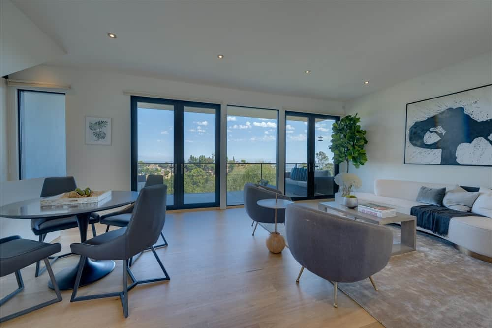 A few steps from the living room is an informal dining area. You can also see here the glass sliding doors leading to the balcony adorned with a potted plant. Image courtesy of Toptenrealestatedeals.com.