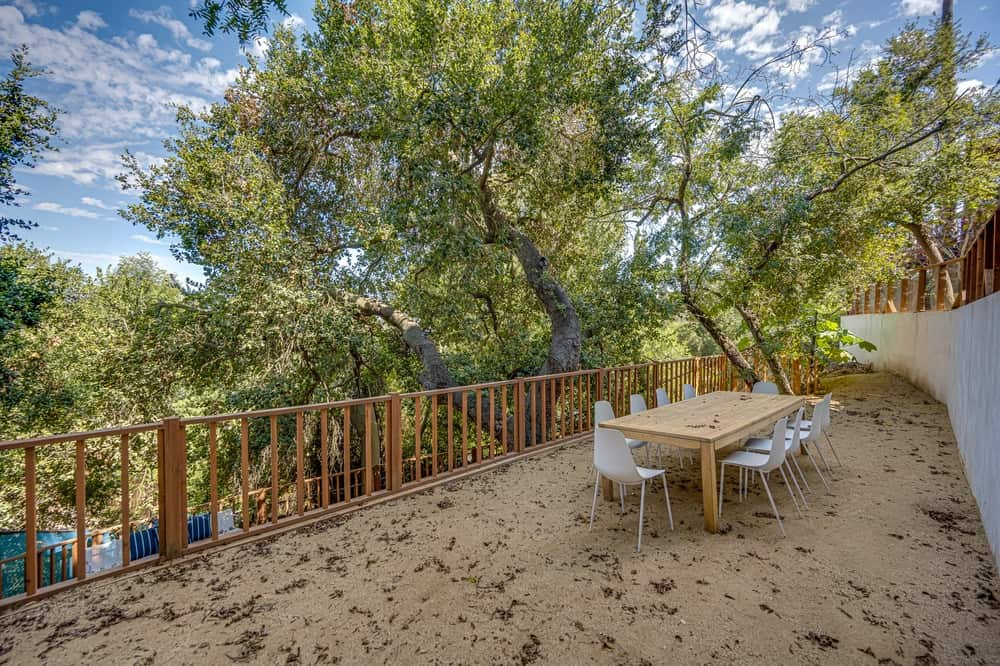 This is a view of the first level balcony deck with a wide space enough for a large outdoor dining area under the shade of tall trees. Image courtesy of Toptenrealestatedeals.com.