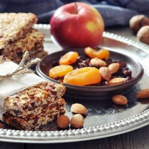 granola bars on a plate with nuts and fruits.