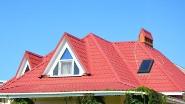 A close look at a house with red hip and valley roof.