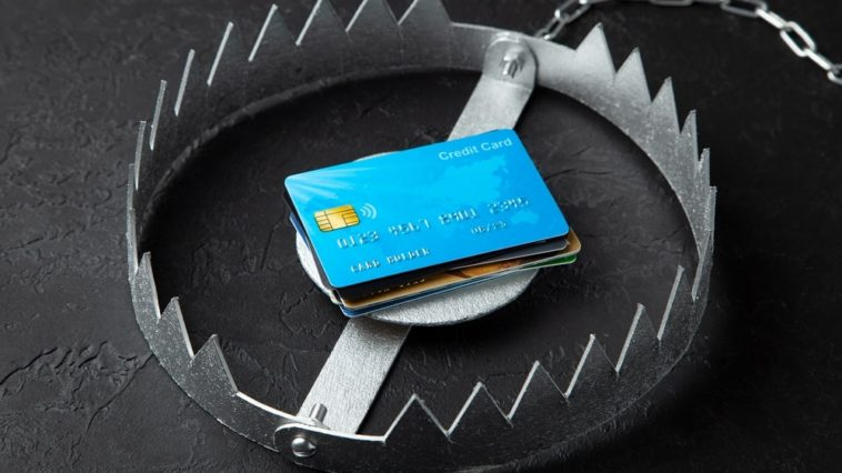 A large steel bear trap with a stack of credit cards as bait.