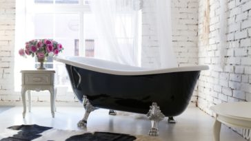 A black claw foot freestanding bathtub at the corner by the window.