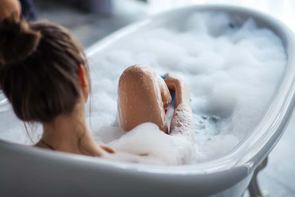 A woman soaking in her freestanding bathtub.