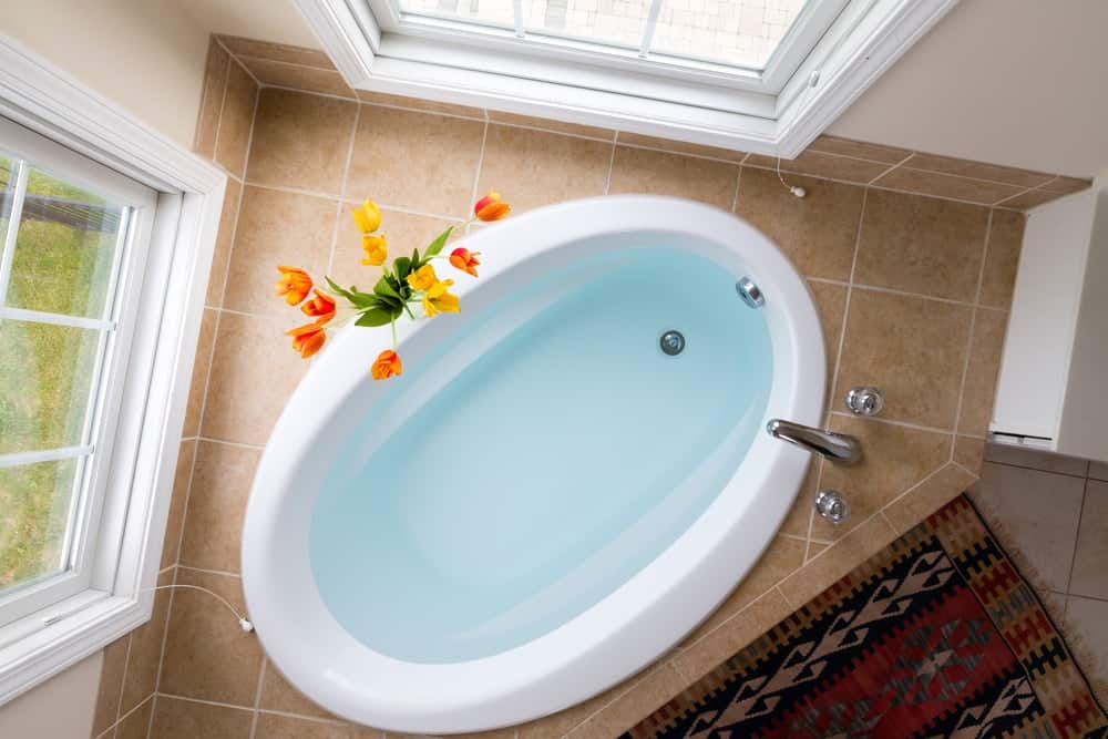 This is a top view of the bathtub that is placed at the corner of the bathroom between two windows.