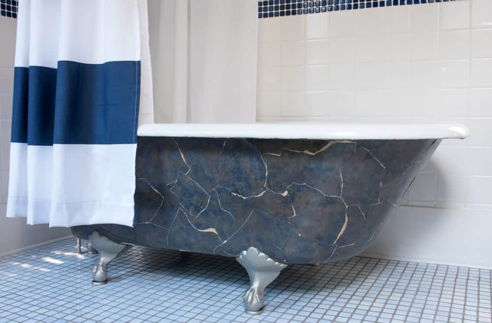 A dark freestanding bathtub with claw feet is paired with a bright shower curtain.