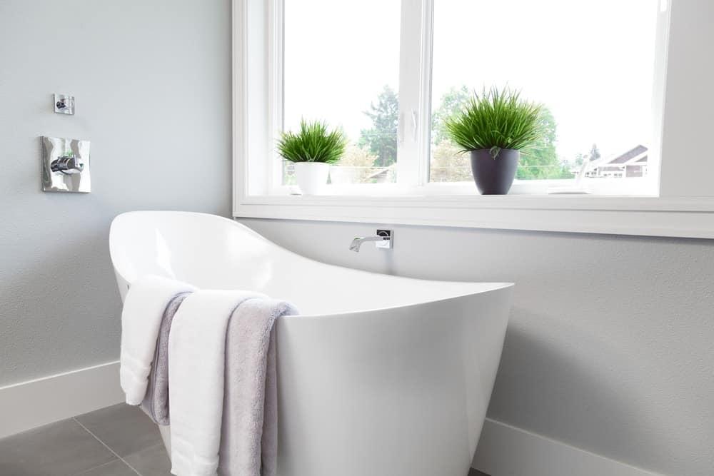 A modern white freestanding bathtub at the corner of the bathroom.