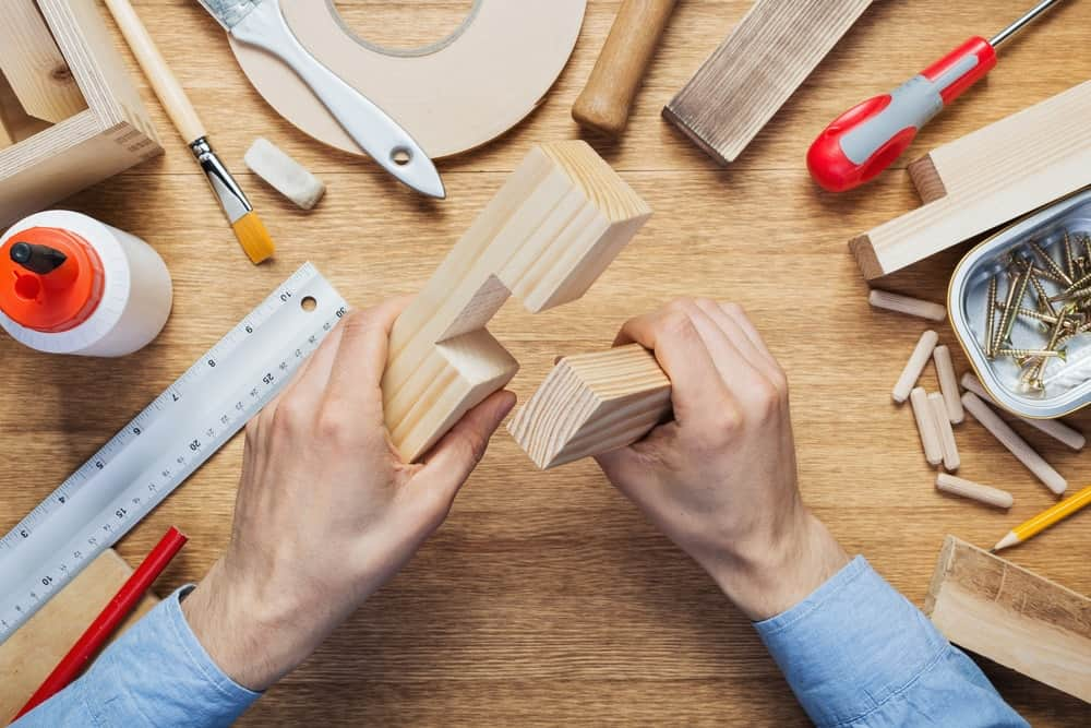 A man working with pieces of wood at a workshop.