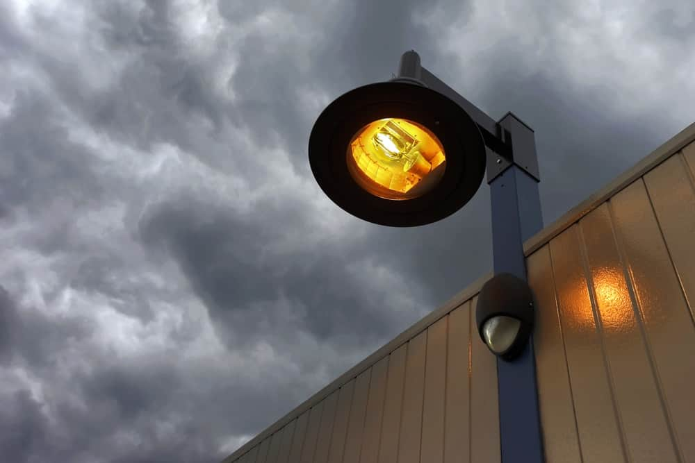 A look at a mercury vapor light bulb on a streetlight warehouse exterior.