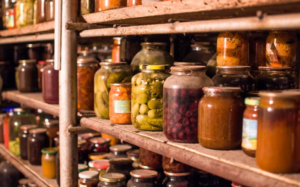 An old pantry with wooden shelves of preserved food.
