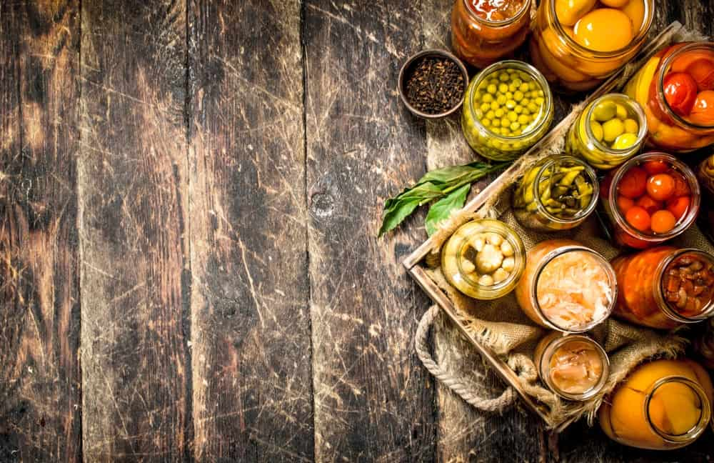 A look at a rustic wooden table with preserved food in jars.