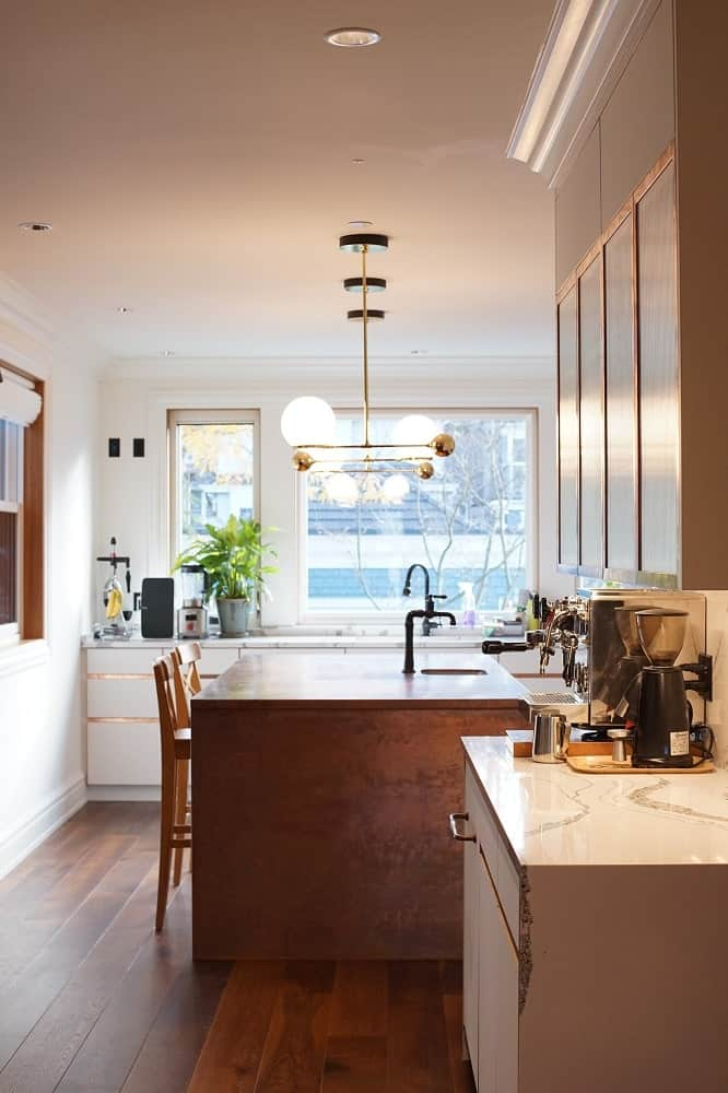 This is a view of the kicthen with a wood-toned kitchen island that matches with the hardwood flooring.