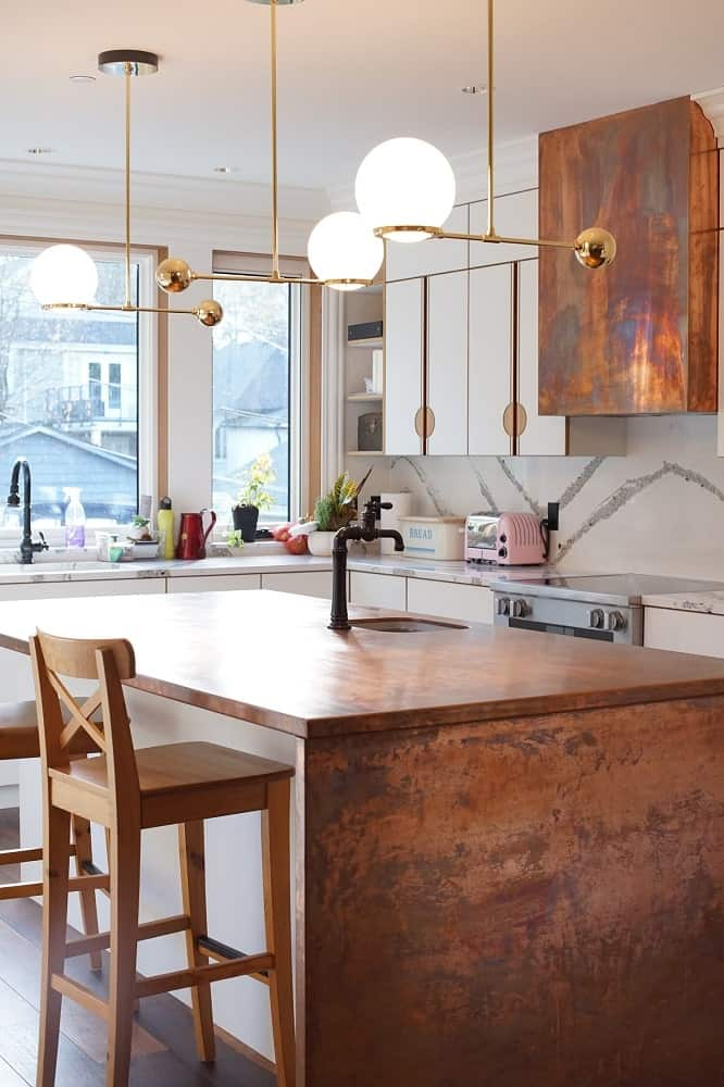 This is a closer look at the earthy tone of the kitchen island adorned with decoraive lights above and paired with wooden stools.