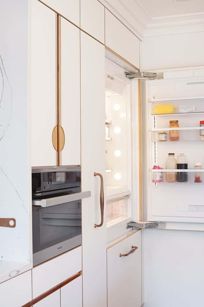 On the other side is the fridge with doors that blend seamlessly with the beige cabinetry of the kitchen.
