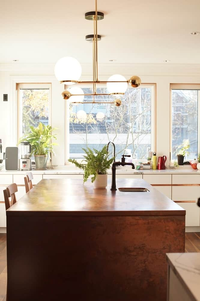 This is a close look at the wooden kitchen island with decorative lighting above, a faucet and sink area adorned with a potted plant.