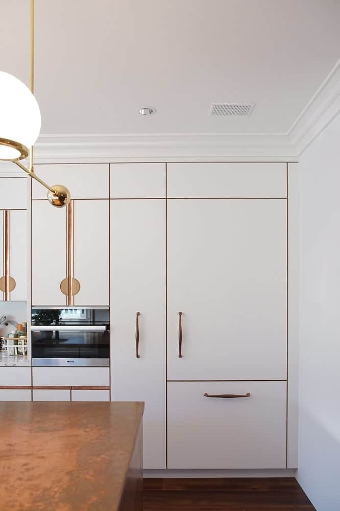 This is a view of the built-in cabinetry from the vantage of the kitchen island showcasing the appliances and the fridge that blends with the cabinetry.