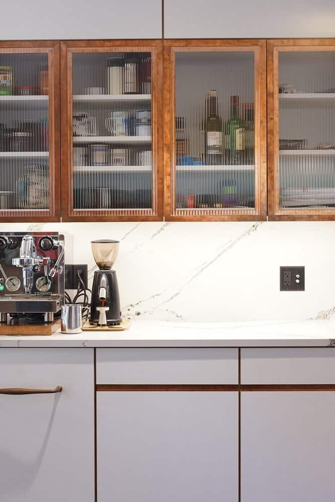 This corner of the kitchen has floating cabinets that has opaque glass panels on its doors and has lighting underneath.
