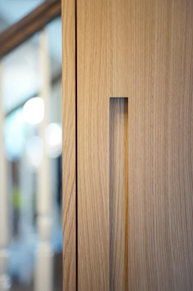 This is a close look at the masterful craftsmanship of the handle of the wooden cabinetry in the dining area.