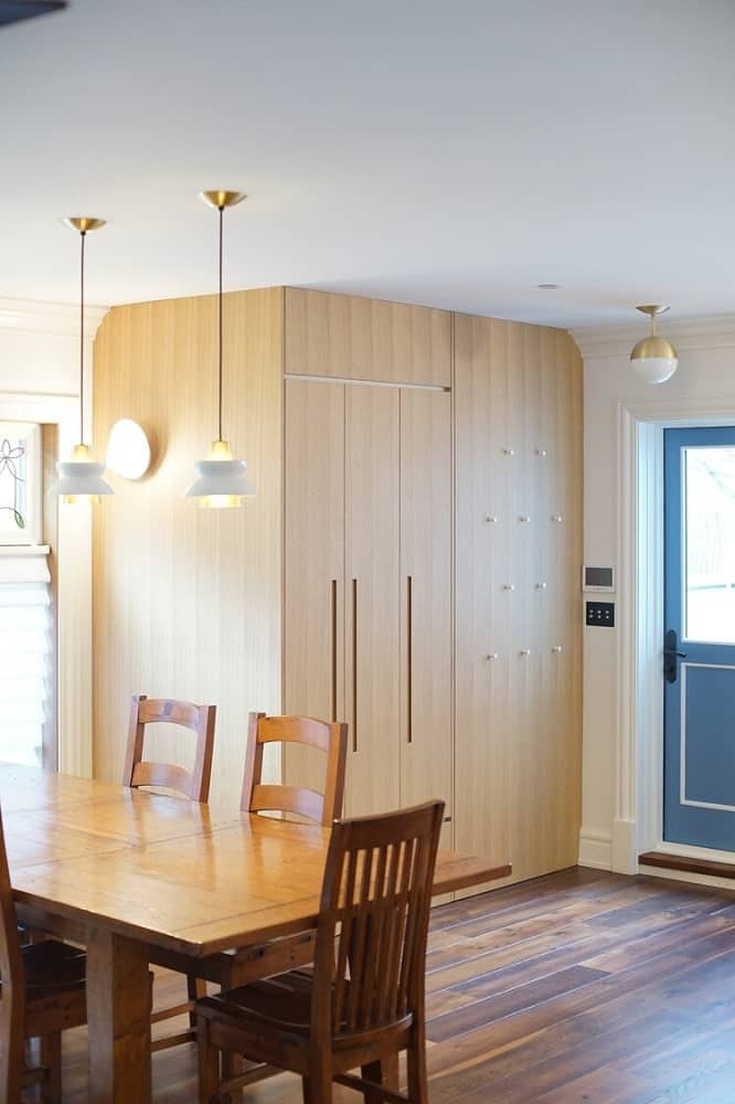 This is a view of the dining area showcasing the proximity of the wooden cabinet from the wooden dining set topped with pendant lights.
