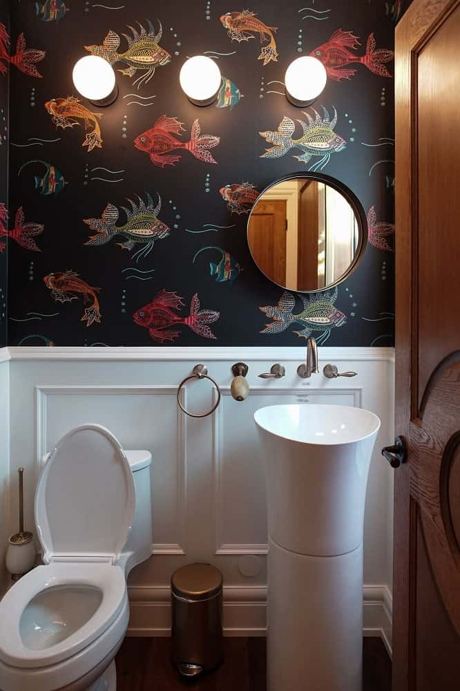 This is the powder room with a dark patterned wallpaper and white wainscoting that matches with the pedestal sink and toilet.