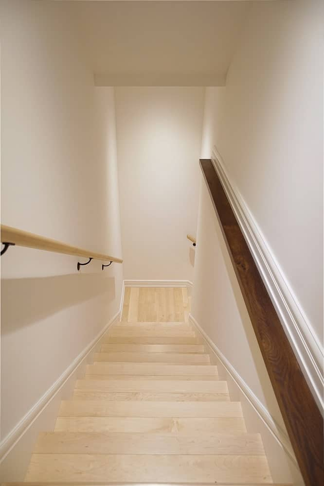 This is a view of the staircase from the vantage of the second floor landing. You can see here that the staircase is enclosed with walls on both sides.