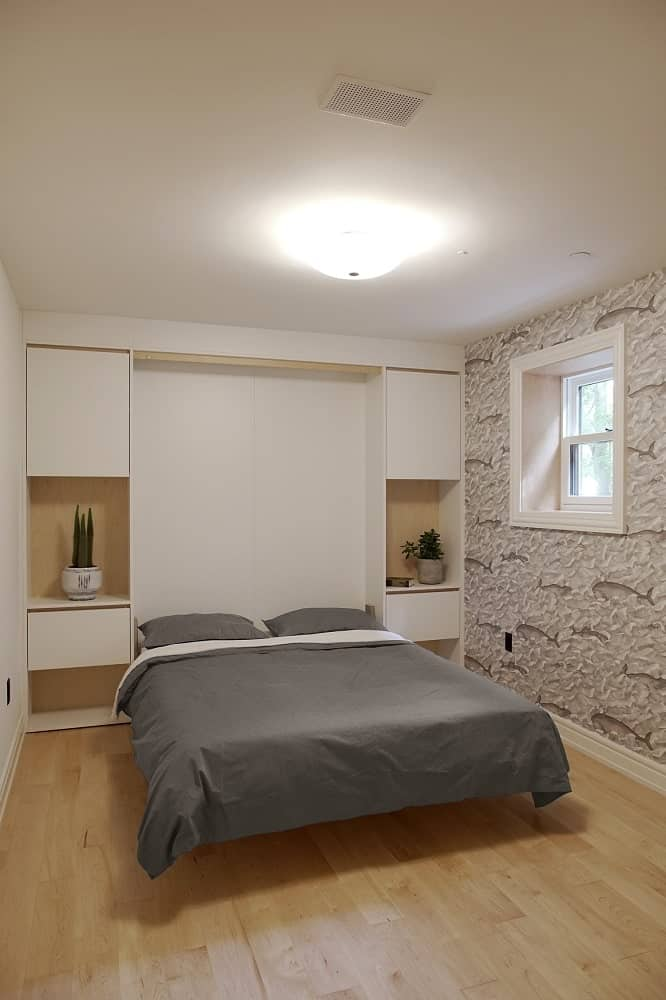This is the bedroom with a simple design to its beige ceiling, beige wall and hardwood flooring making the gray bed stand out.