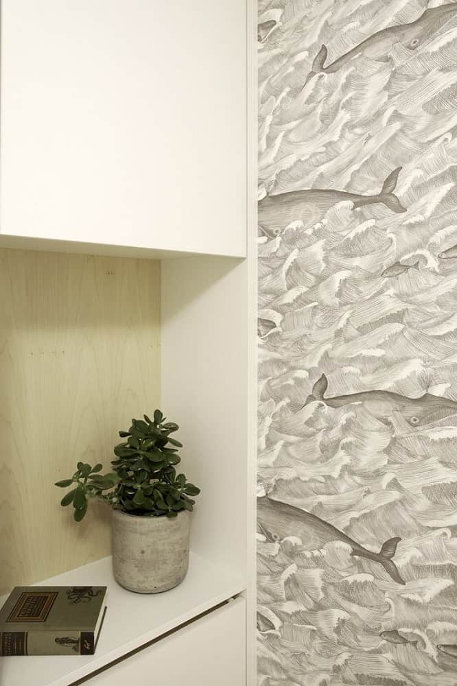 This is a close look at the built-in shelf on the side of the Murphy bed adorned with a potted plant. This view also shows the wallpaper on the side wall.