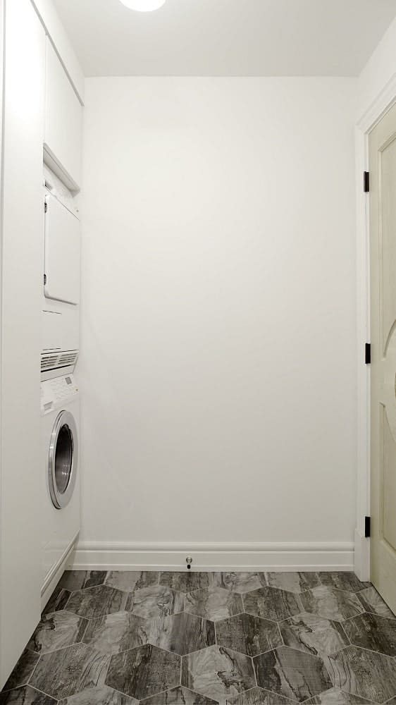 This is the laundry room with a gray flooring that complements the beige walls that blend with the washers embedded into the wall at the corner.