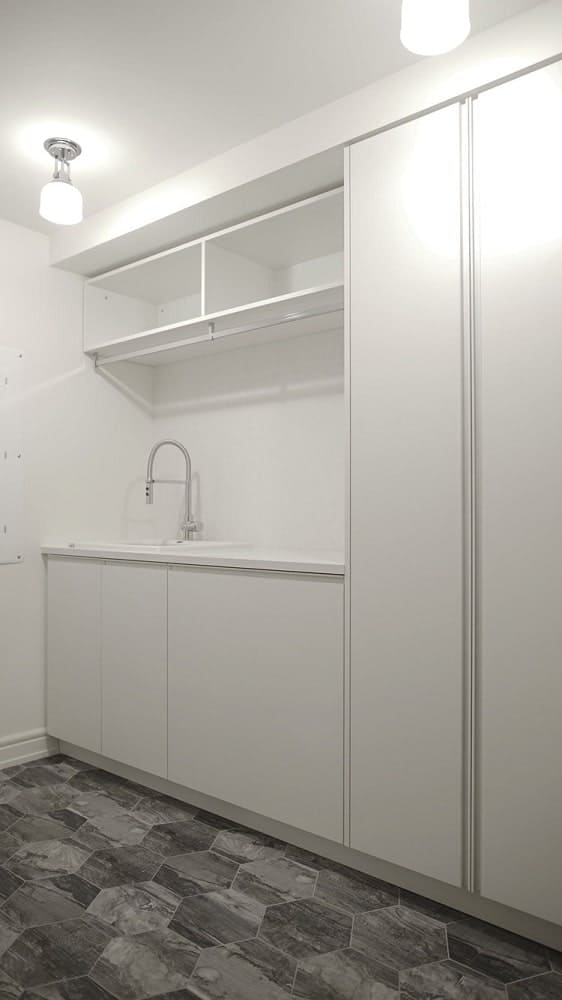 On the other side of the embedded machines is a small sink area with shelves above and cabinets on the side.