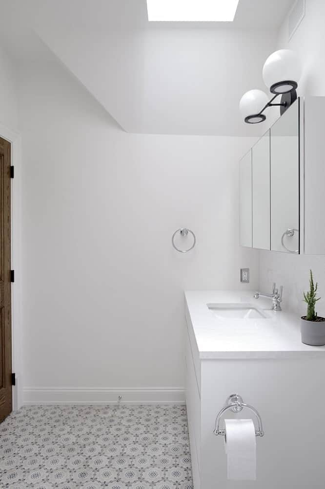 This is the white vanity of the bathroom topped with mirrors and lights.
