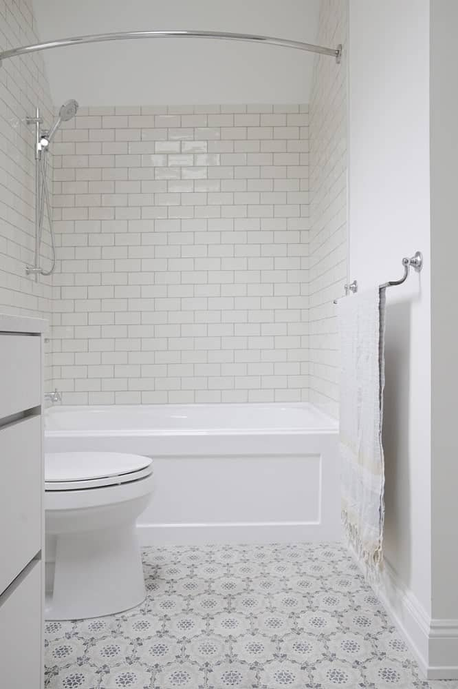 This is a look at the toilet and bathtub of the bathroom that is adorned with white subway tiles.
