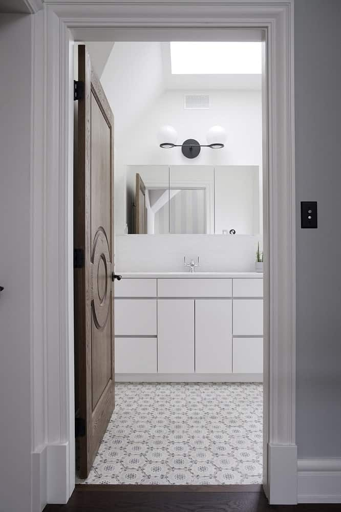 This is a look at the bathroom from the vantage of the dark wooden door with carved patterns. This provides a nice contrast to the modern cabinetry of the bathroom vanity.