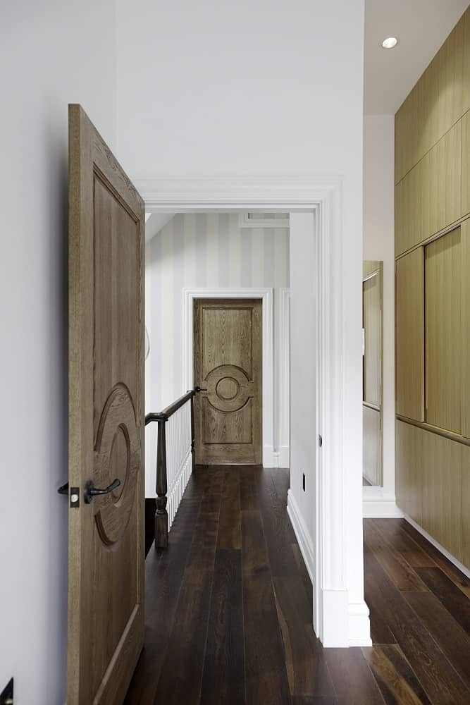 This is a look at the hallway and landing of the second level with wooden doors and hardwood flooring adorned by bright striped wallpaper.