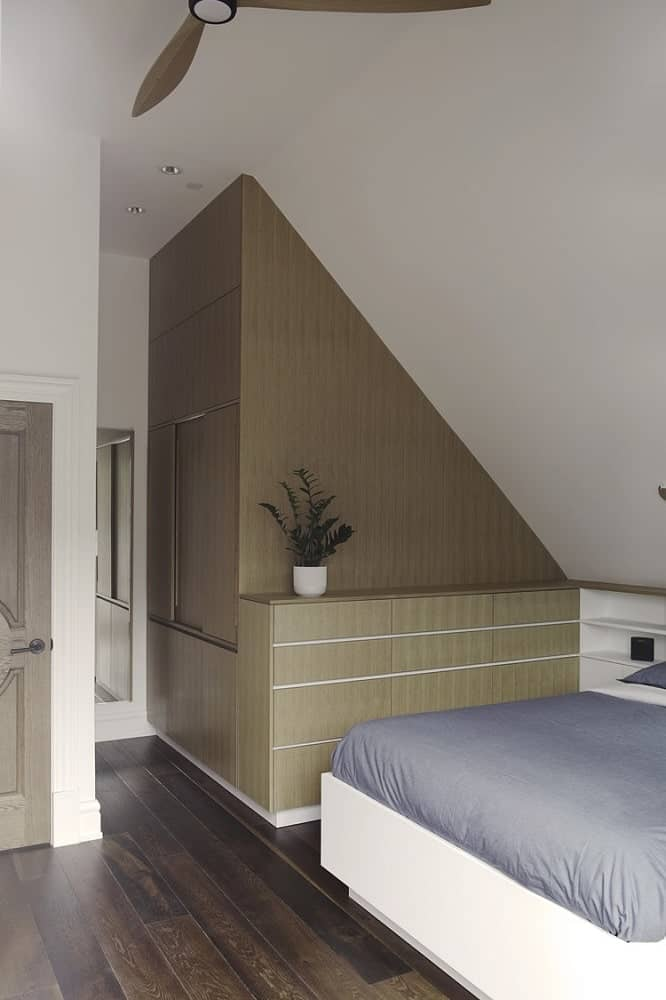 This view of the bedroom shows the built-in cabinets at the side of the bed and the bed frame that is brightly-toned to contrast the dark hardwood flooring.