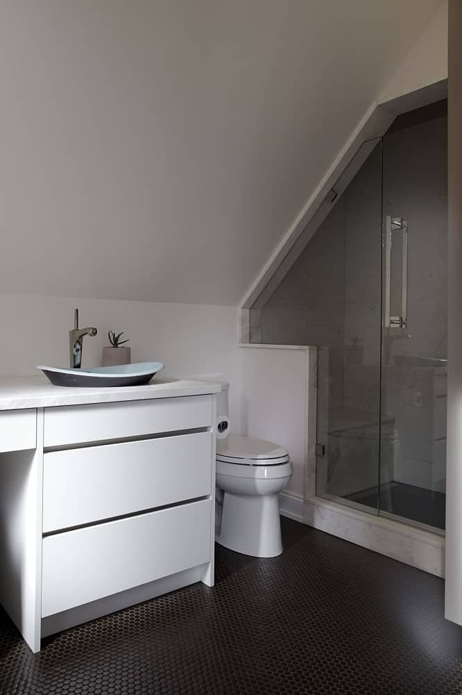 The vanity has a freestanding sink on the side above the drawers.