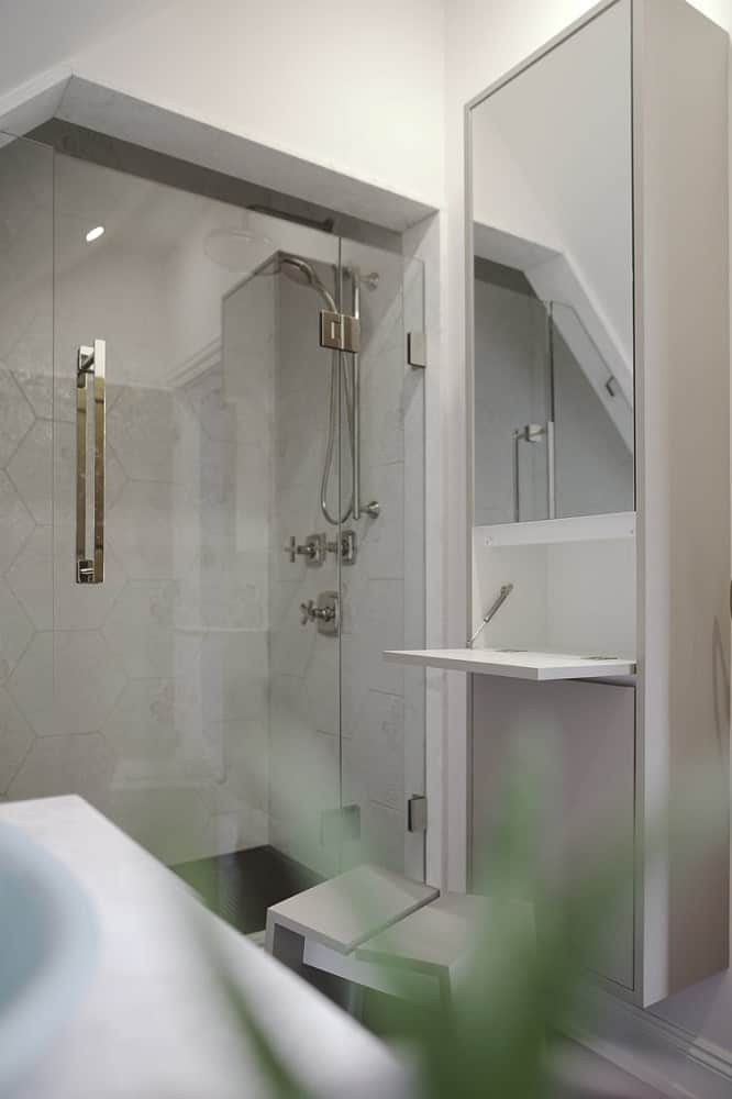 At the side of the vanity is the toilet and followed by the glass-enclosed shower area.