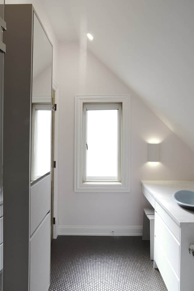 This is a view of the small bathroom from the vantage of the shower area showcasing the shed ceiling and the window on the far side.