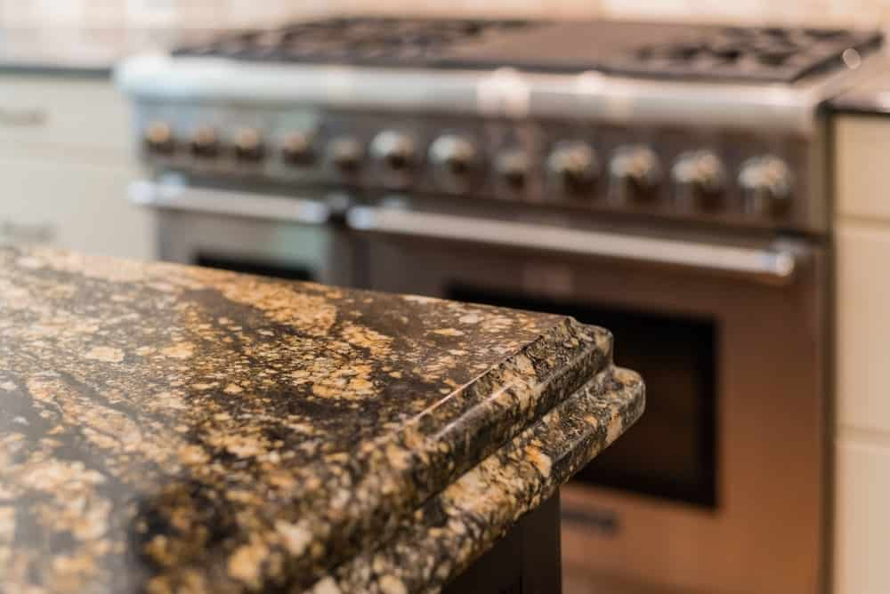 A close look at a kitchen island with granite countertop.