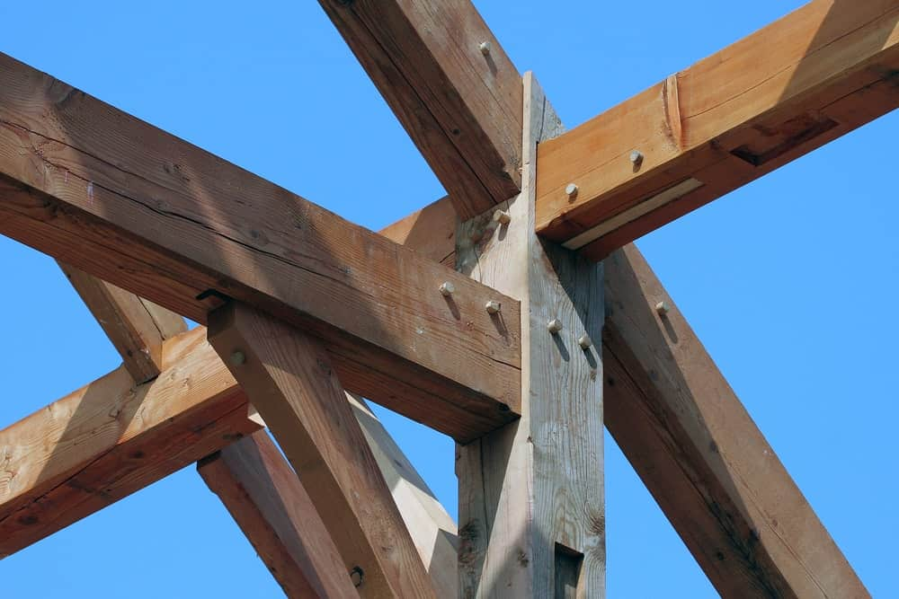 A close look at the timber frame of a house with tenon joints.