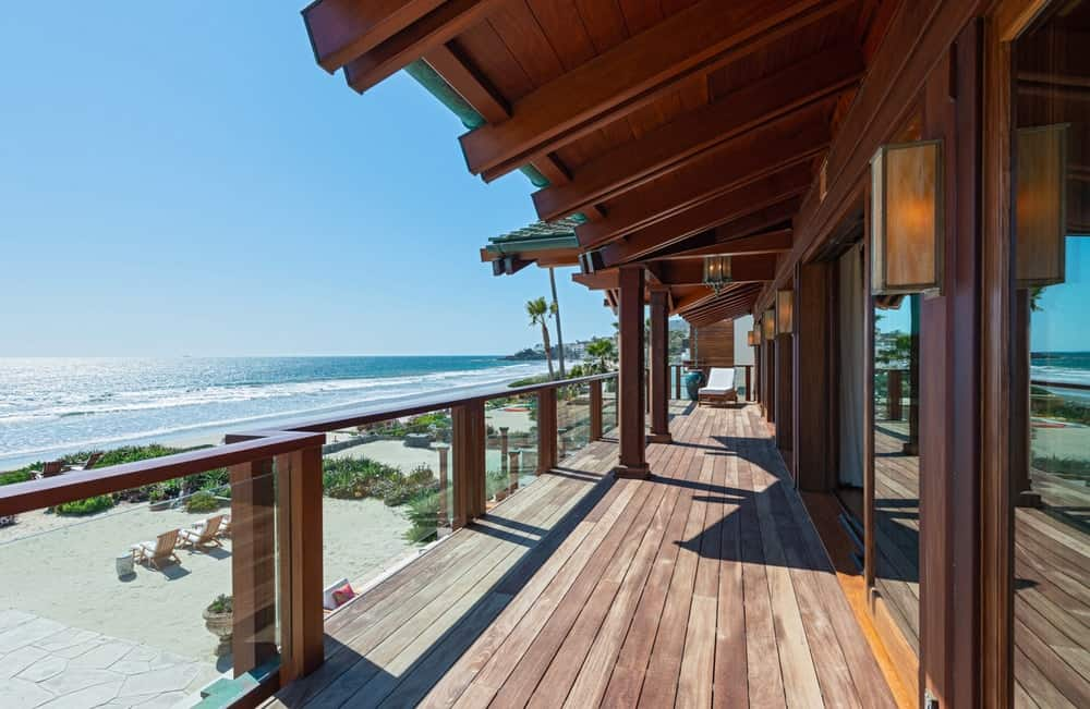 This is the balcony that faces the ocean with wooden elements and glass railings to maximize the view. Image courtesy of Toptenrealestatedeals.com.