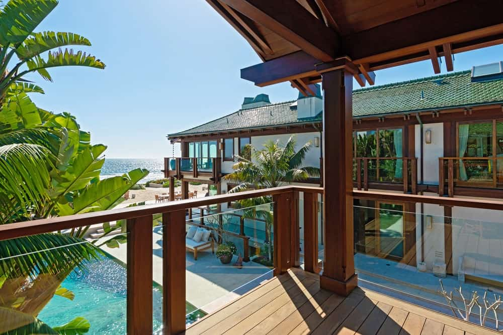 This balcony looks over the poolside area with a full view of the pool and the surrounding tropical landscape that brings color to the house exterior. Image courtesy of Toptenrealestatedeals.com.